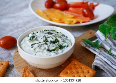 Homemade Spinach dip served with crackers and veggies, selective focus