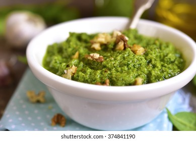 Homemade spinach pesto with walnut in a white bowl.