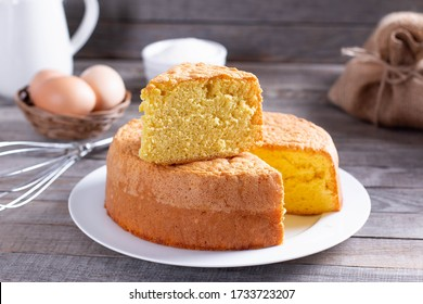 Homemade sponge cake on a white plate on a wooden table