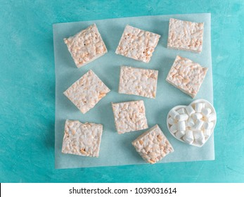 Homemade square bars of Marshmallow and crispy rice and ingredients on azure blue background. American dessert with marshmallow and crispy rice. Top view. Copy space