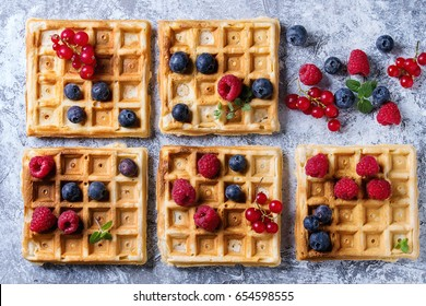 Homemade square belgian waffles with fresh ripe berries blueberry, raspberry, red currant over gray texture background. Top view with space