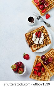 Homemade square Belgian waffles with ricotta cheese, chocolate, strawberries and cherries for breakfast on a light concrete background. Selective focus.Top view. Cope space.
