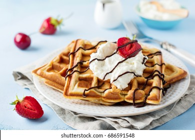 Homemade square Belgian waffles with ricotta cheese, chocolate, strawberries and cherries for breakfast on a light concrete background. Selective focus.