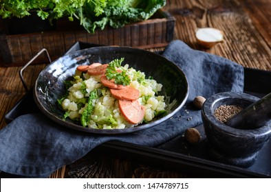 Homemade Stamppot, traditional Dutch meal made from mashed potatoes and curly kale, served with sausage slices