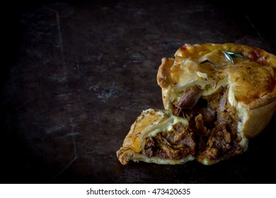 Homemade Steak and Cheese Pie Sliced on Rustic Baking Tray, Copy Space, Vertical