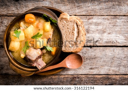 Homemade stew soup with vegetables and beef ribs in the rustic bowl,selective focus and blank space