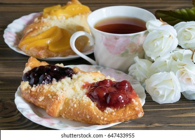 Homemade strawberry and blueberry danish pastry with cup of tea and yellow roses on wooden table.Lovely afternoon tea.