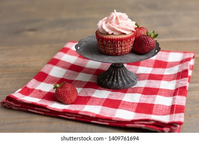 Homemade Strawberry Cupcake on Metal Pedestal with Fresh Strawberries on Red and White Checked Napkin on Wooden Table