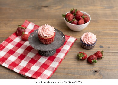 Homemade Strawberry Cupcake on Metal Pedestal on Red and White Checked Napkin; Another Cupcake and Fresh Strawberries in Background; Wood Table