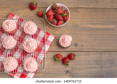 Homemade Strawberry Cupcakes on Wire Rack with Bowl of Fresh Strawberries Beside on Red and White Checked Napkin on Wood Table