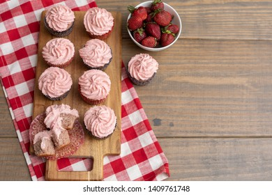 Homemade Strawberry Cupcakes on Wood Cutting Board with one Broken Open; Bowl of Fresh Strawberries; Red and White Checked Napkin on Wooden Table