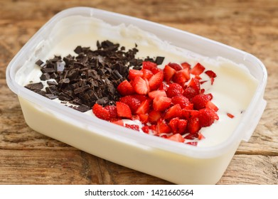 Homemade strawberry ice cream with chocolate in a plastic container on a wooden background