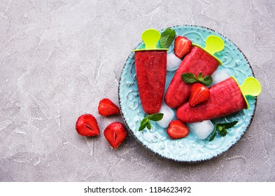 homemade strawberry ice cream and fresh strawberries on a table