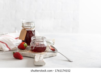 Homemade strawberry jam or marmalade in the glass jars and ripe strawberries on the wooden board on white background. Side view, copy space for text or product. Cookbook recipe. Preserve food. Banner