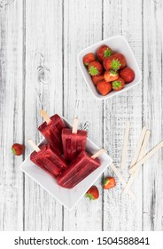 Homemade Strawberry Popsicles (close-up shot; selective focus) on vintage background