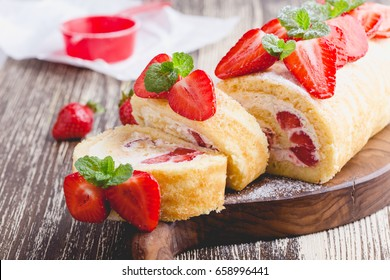 Homemade strawberry shortcake cake roll with cream cheese whipped cream, perfect summer season dessert served on rustic wooden board