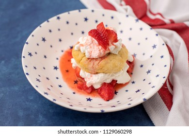 Homemade Strawberry Shortcake topped with Whipped Cream; Red and White Striped Towel; Blue Background
