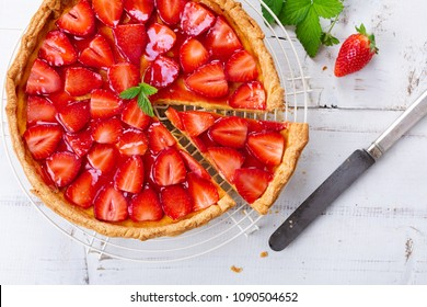 Homemade strawberry tart decorated with strawberry leaves. Top view
