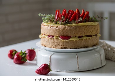 Homemade strawberry and vanilla custard cream sponge cake on white table.