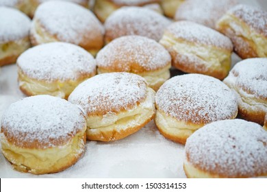 Homemade stuffed donuts on a parchment covered table. Round donuts sprinkled with white icing sugar with fruit jam. Sweet baking department in the store.