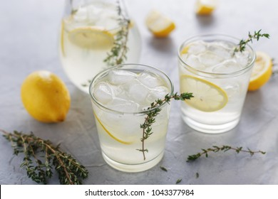 Homemade summer drink with lemon, thyme and ice in the glasses on the table. Refreshment detox cocktail.