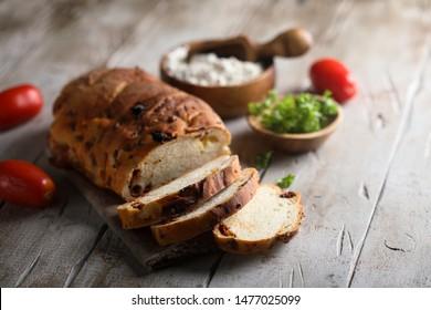 Homemade sun-dried tomatoes bread on wooden desk - Shutterstock ID 1477025099