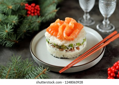Homemade sushi cake with lightly salted salmon, avocado, soft cheese and seaweed. Christmas background.