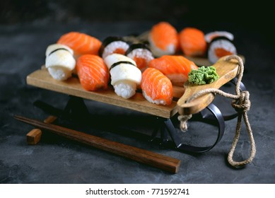 Homemade sushi nigiri and rolls with salmon and fried squid on decorative sleigh, christmas background.