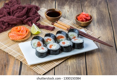 Homemade sushi rolls with salmon, cream cheese and cucumber filling, covered with nori leaf. Fast food delivery concept