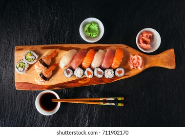 Homemade sushi with salmon, smoked eel, curd cheese and vegetables on stone background