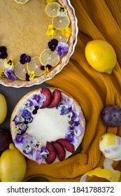 Homemade sweet cakes on a table. Close up photo of lemon tart, cheesecake decorated with flowers and fresh citrus fruits on yellow fabric background.