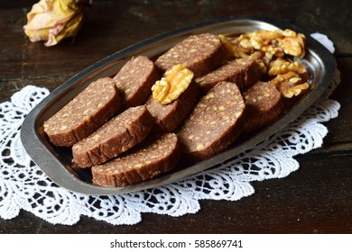 Homemade sweet chocolate sausage cut in pieces on a metal tray and on a wooden background