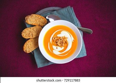 Homemade sweet potato and carrot soup with chili and ginger decorated by sour cream and roasted peanut in white bowl laying on the concrete tray with blue napkin with whole grain crackers