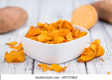 Homemade Sweet Potato Chips on vintage background selective focus; close-up shot