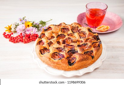 Homemade sweet round plum cake New York Times on plate with glass of tea, coffee and flowers on family breakfast or birthday, holyday party on white vintage table in country style. Selective focus.
