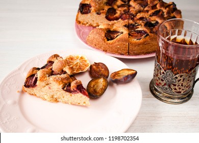 Homemade sweet round plum cake New York Times cutted with cups, glasses of tea, coffee on saucers on family holyday Breakfast or birthday party on white table country style. Side veiw. Selective focus