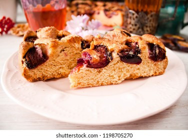 Homemade sweet round plum cake New York Times cutted slices on plate with cups, glasses of tea, coffee and flowers at back side on holyday breakfast or birthday party on white table. Selective focus.
