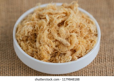 Homemade sweet and soft dried shredded pork or pork floss on white plate put on sack in close up view macro concept to present texture. Thai style delicious food for cooking or bakery.