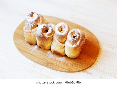 Homemade sweet swirly buns with raisins, cherries and cranberries sprinkled with powdered sugar on white wooden table. Shallow focus.