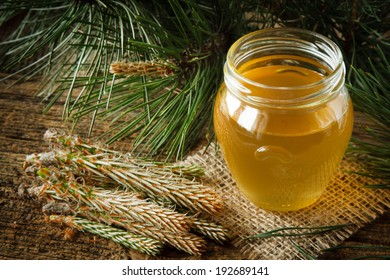Homemade syrup made from green young pine buds and sugar. Focus on jar