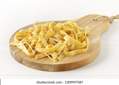 Homemade tagliatelle on chopping board