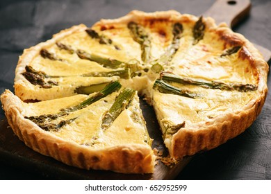 Homemade tart with asparagus and cheese on black background.