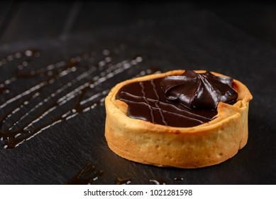 Homemade tart  with dark chocolate on a dark background