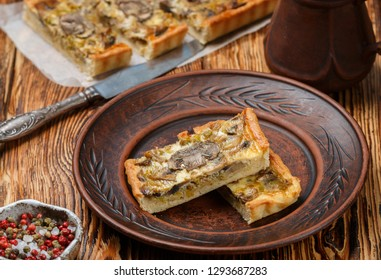 Homemade tart with mushrooms, leek, cheese and thyme on rustic background. Traditional snack cake. Lunch or dinner for gourmets. Selective focus