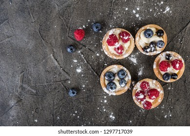 Homemade  tartlets with berries on gray  background, top view