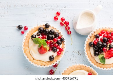 Homemade Tartlets with cream and fresh berries - ripe red and black currants, strawberries on blue rustic wooden background, top view