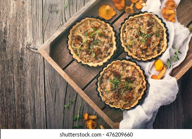 Homemade tarts of puff pastry with seasonal chanterelle mushrooms, cheese, thyme and onion on rustic wooden table, top view