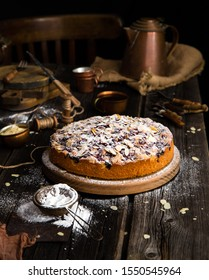 homemade tasty biscuit round cake with cherries, almond flakes, powdered sugar