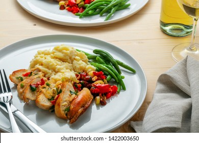 Homemade tasty chicken fillet with green beans, mashed potato and vegetable sauce on two round white plates. Traditional healthy meal with white wine.