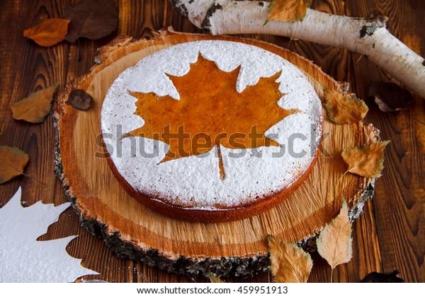 Homemade tasty manna pie  with a sugar powder (stencil of a maple leaf) on birch saw cut. Selective focus